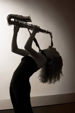 Portrait of woman playing saxophone, sepia toned.