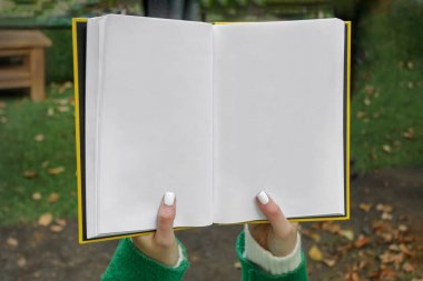 Hands holding an open book with blank pages - a place to insert your text. Young woman reads a book