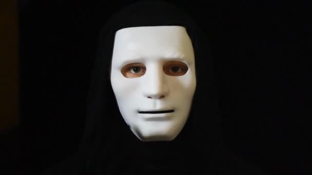 Mann im Dunkeln mit weißer Maske