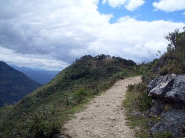 End of the 9.8 km pedestrian path with the first view of the Kuelap fortress, cloudy sky and extraordinary view of the Andes mountain range