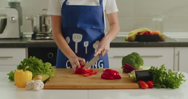 Egy nő egy nagy borsot szeletel a konyhaasztalon. Salátakészítés. 4K