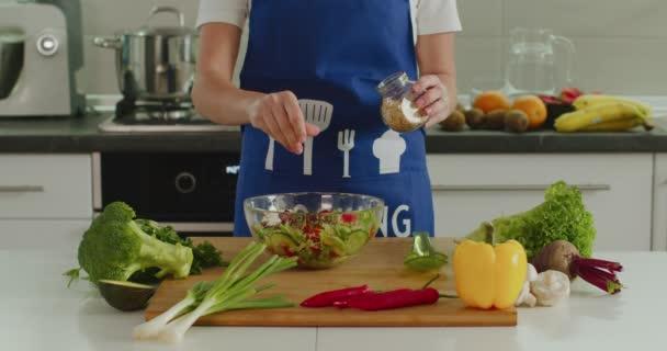 Žena sype sezamová semínka na salát. Příprava salátu. 4K