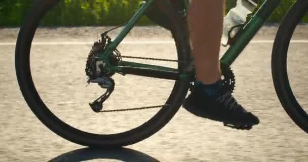 Közelkép a biciklislábakról. Pedálozik és forog a kerék. Biciklivel edzek. 4K