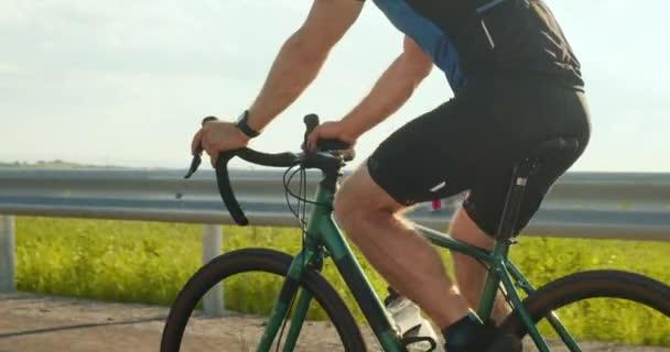 Po dálnici jede sportovec na kole. Detailní záběr na cyklistické nohy. Trénink na kole. 4K