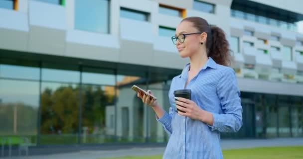 Egy üzletasszony sétál és SMS-ezik az okostelefonján. Egy csésze kávét tart a kezében. Üzleti központ a háttérben. 4K
