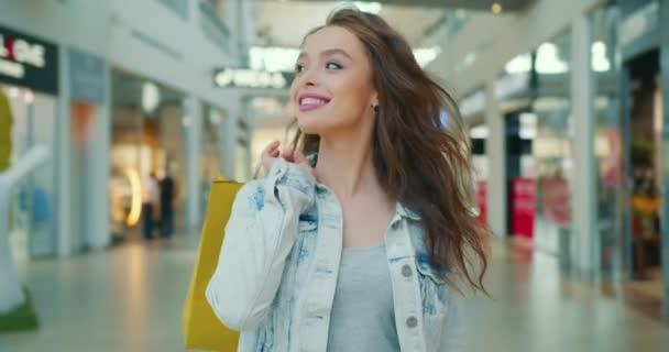 Das Mädchen lächelt und läuft durch das Einkaufszentrum. Sie wirft Einkaufstüten über ihre Schulter. 4K