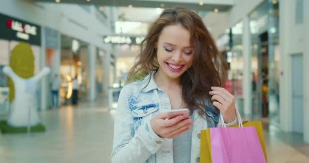 Ein lächelndes Mädchen telefoniert und läuft durch das Einkaufszentrum. Sie hält Einkaufstüten in der Hand. 4K