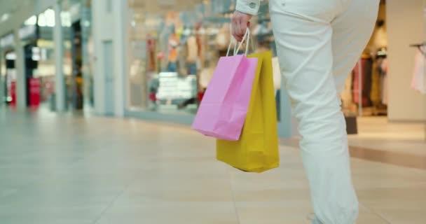 Ein Mädchen läuft durch das Einkaufszentrum und trägt Einkaufstüten. Nahaufnahme. 4K