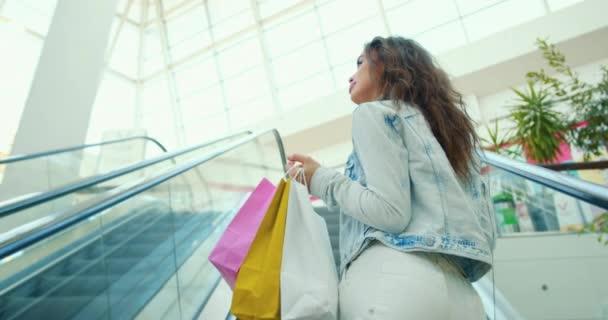 Das Mädchen fährt die Rolltreppe hoch und hält Einkaufstüten in der Hand. Sie lächelt. 4K