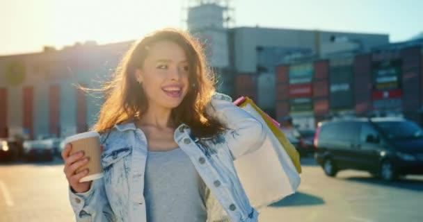 Ein Mädchen läuft mit einer Tasse Kaffee über den Parkplatz eines Einkaufszentrums. Sie lächelt und trägt Einkaufstüten. Im Hintergrund scheint die Sonne. 4K