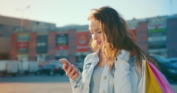 Das Mädchen schreibt SMS auf ihrem Smartphone und lächelt. Sie steht auf dem Parkplatz eines Einkaufszentrums und hält Einkaufstüten auf ihrer Schulter. 4K