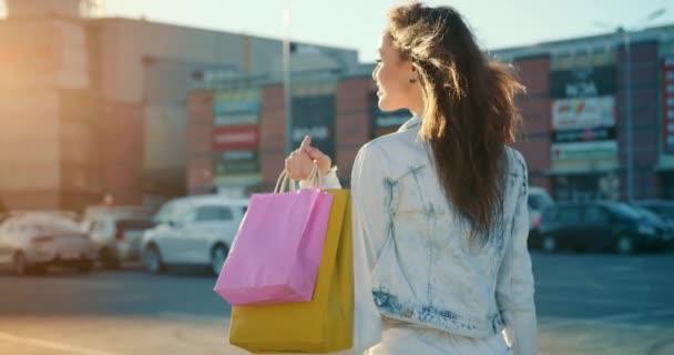 Das Mädchen läuft lächelnd über den Parkplatz des Einkaufszentrums. Sie hält Einkaufstüten in der Hand. Der Wind bläst ihr durch die Haare. 4K