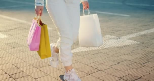 Close-up of a girls feet walking in the parking lot. She has shopping bags in her hands. 4K