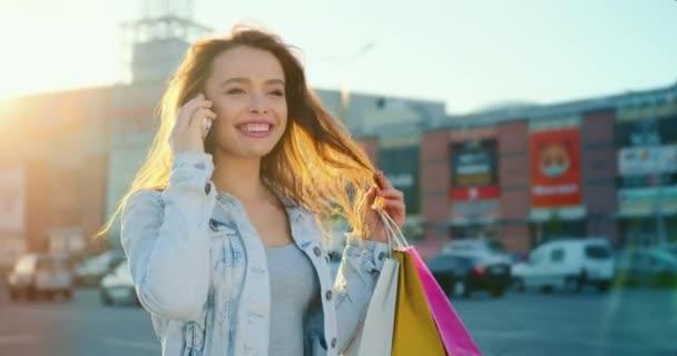 Das Mädchen telefoniert emotional. Sie lächelt und justiert ihre Haare. Sie hält Einkaufstüten in den Händen. Im Hintergrund ein Einkaufszentrum. 4K