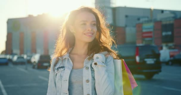 Dívka stojí a usmívá se. Drží nákupní tašky. Slunce svítí v pozadí. 4K