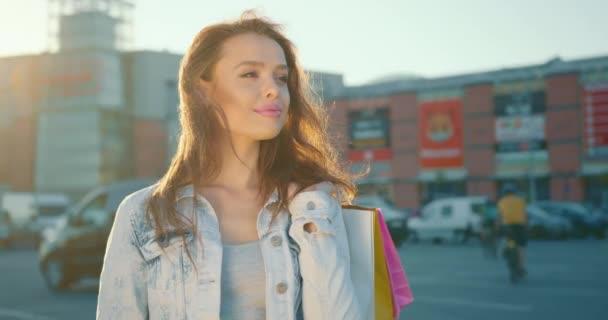 Das Mädchen steht auf dem Parkplatz eines Einkaufszentrums. Geschäfte mit Einkaufstüten. Im Hintergrund scheint die Sonne. 4K