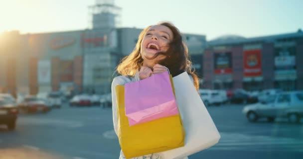 Dívka se usmívá. V rukou drží nákupní tašky. Stojí na parkovišti v nákupním centru. Slunce svítí v pozadí. 4K