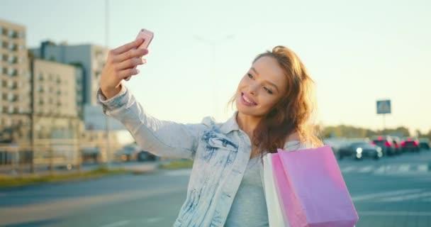 Ein Mädchen macht ein Selfie mit ihrem Handy. Sie steht auf dem Parkplatz des Einkaufszentrums und hält Einkaufstüten in der Hand. 4K