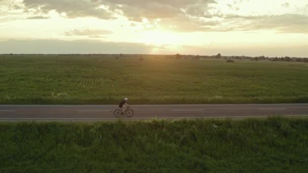 Sportovec jezdí na kole. Západ slunce v pozadí. Střílí z dronu. 4K