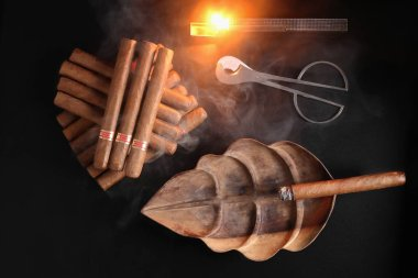 ZENITHAL PHOTOGRAPHY OF  CUBAN CIGAR IN A WOODEN ASHTRAY SHAPED LIKE A LEAF NEXT TO A GROUP OF CIGARS A CIGAR CUTTER AND A LIGHTED LIGHTER
