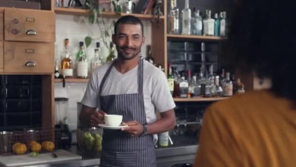 männlicher Barista serviert dem Kunden Kaffee am Tresen