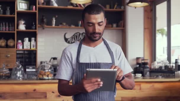 männlicher Besitzer in seinem Coffeeshop mit digitalem Tablet