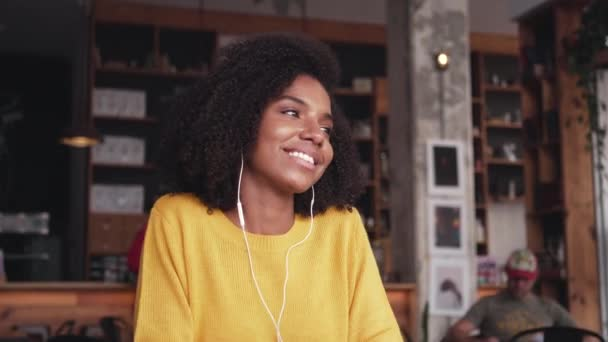 Smiling young woman listening music on earphone in cafe