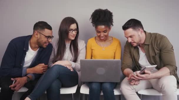 Skupina rozmanitých mladých dospělých přátel, kteří sedí a dívají se na notebook, který pracuje společně na přenosném počítači uvnitř