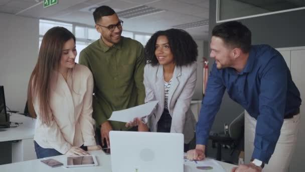 Skupina vícerasových úspěšných mladých obchodních lidí diskutuje o finanční zprávě na pracovišti během setkání v moderní kanceláři
