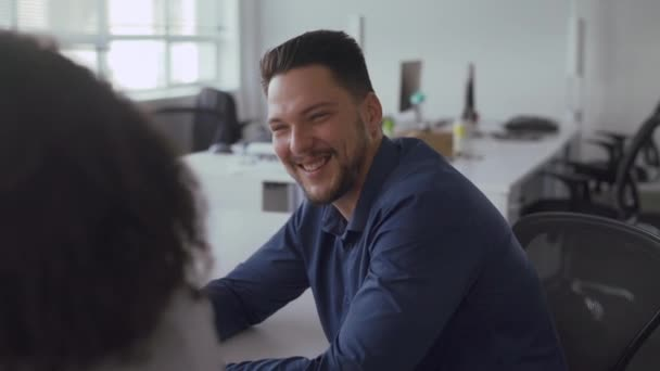 Professional young businessman sitting at table discussing work with female colleague smiling at workplace