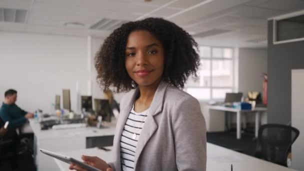 A digitális tabletta az irodában és kollégáinkkal dolgozó boldog ifjú szakmai üzletasszony portréja