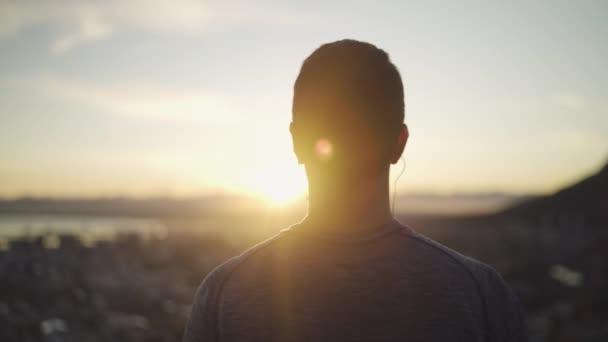 zblízka pohled na atletického fitness muže s sluchátkem v uších a s pohledem inspirující krajinu-muž obdivující východ slunce