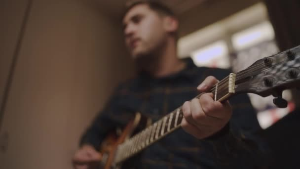 Young man playing an acoustic guitar at home with focus on hand and headstock