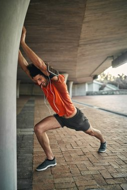 Side view of a cheerful fitness young male runner with electronic devices stretching his hand on column under the bridge