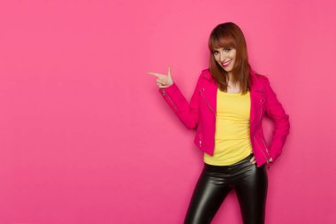 Smiling young woman in yellow shirt, pink jacket and black leather trousers is pointing and looking at camera. Three quarter length studio shot on pink background.