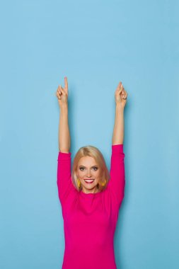 Beautiful blond woman in pink sweater is standing, looking at camera, and pointing up. Waist up studio shot on blue background.