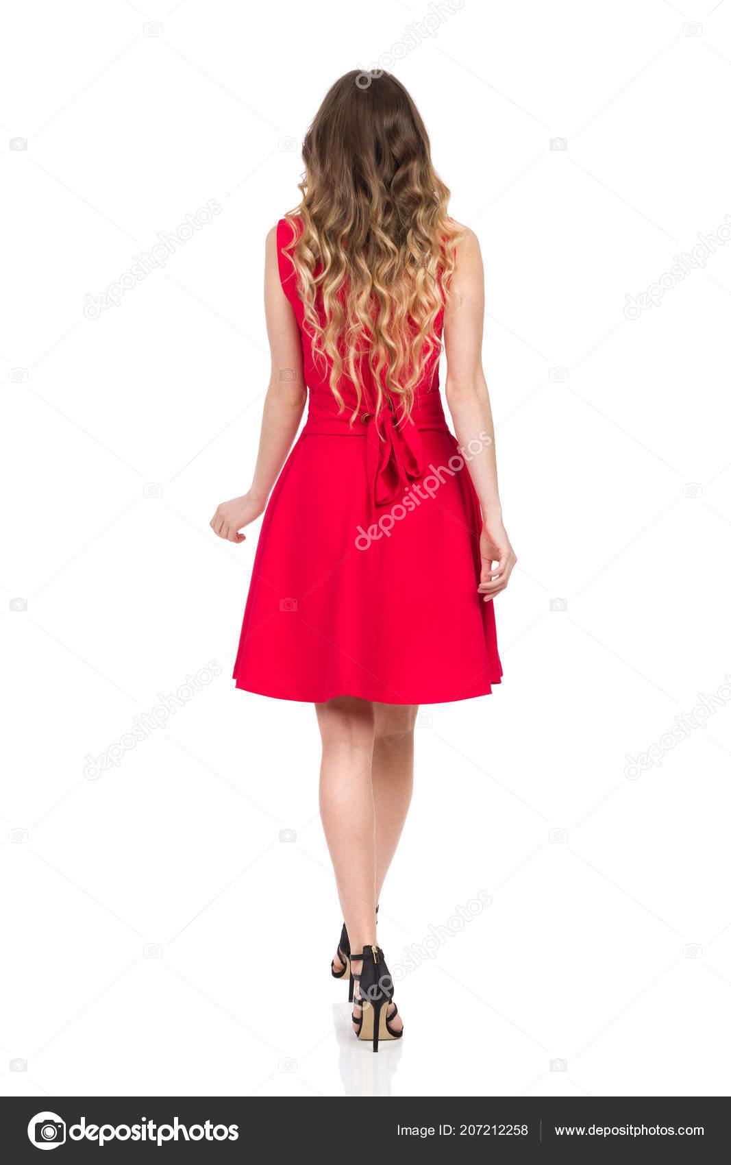 de879abf6527 Krásná mladá žena v černé vysoké podpatky a červené mini šaty je chůze.  Zadní pohled. Po celé délce studio zastřelil izolované na bílém– stock  obrázky