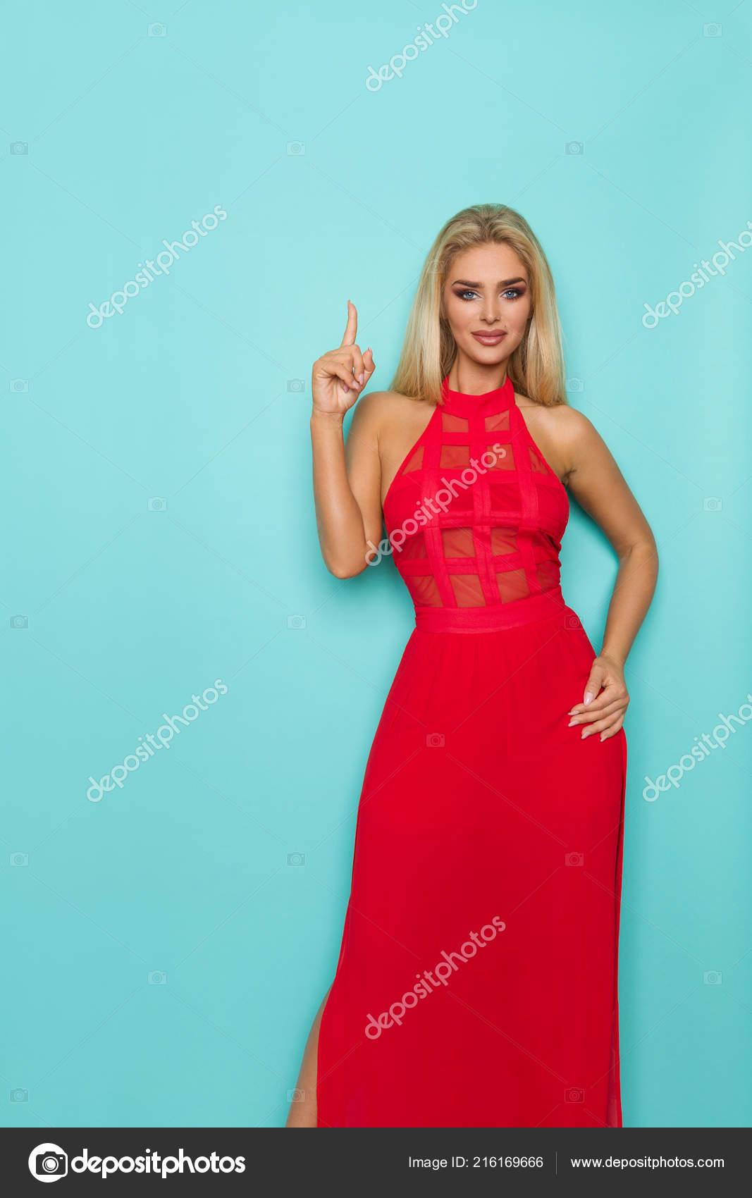 Hermosa mujer rubia en vestido rojo está apuntando hacia arriba y mirando a  cámara. Tres cuartos estudio longitud tiro sobre fondo turquesa — Foto de  ... b8fc1b93ea85