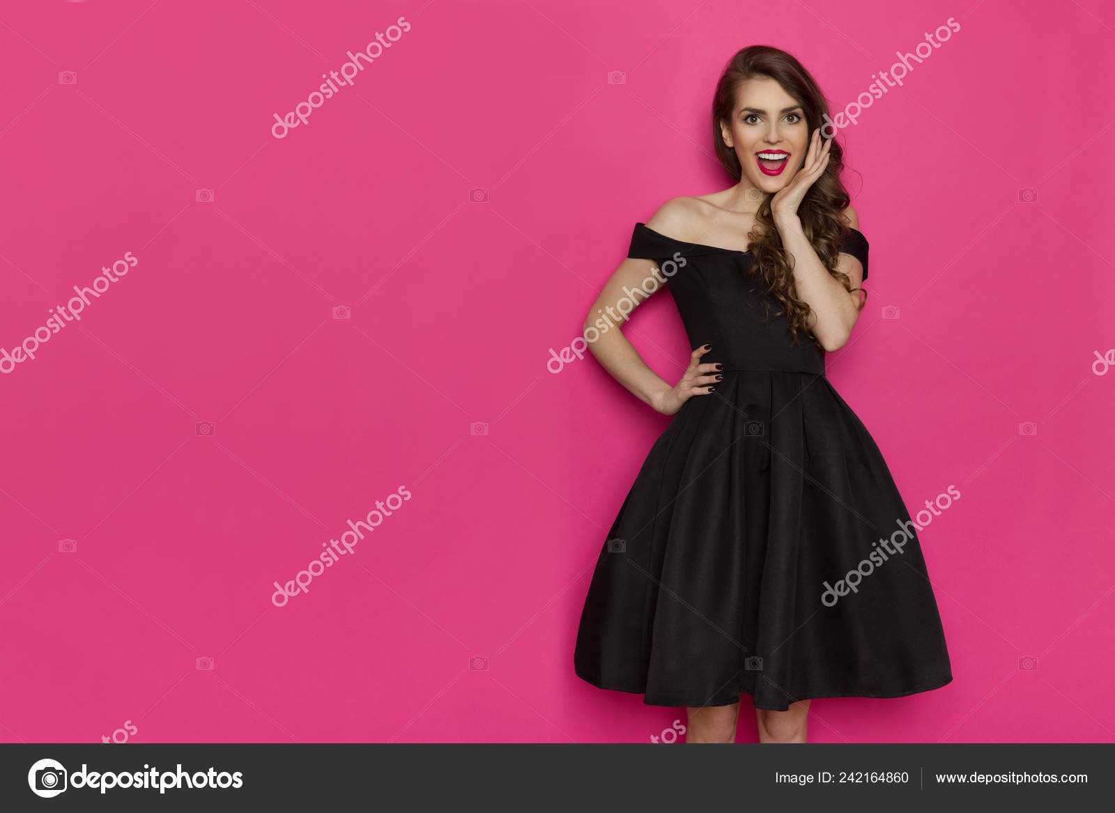 59c8adce961 Surpris belle jeune femme en robe de cocktail noire élégante est maintenant  la main sur hin