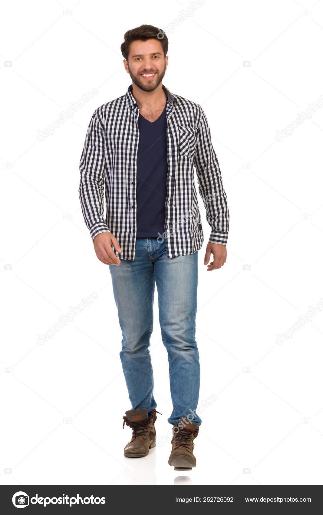 a7ecda5248 Giovane uomo in stivali, jeans e Lumberjack camicia è camminare ...