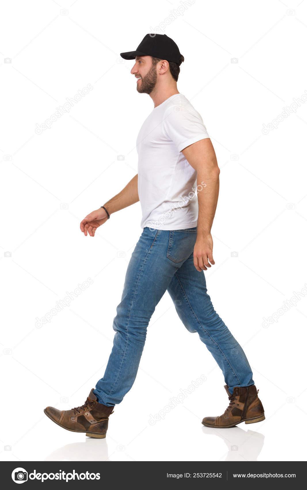 Hombre camina feliz en camiseta blanca, pantalones vaqueros
