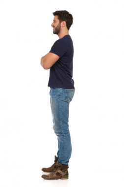 Young Man In Jeans And Blue T-shirt Is Standing With Arms Crossed And Looking Away. Side View.