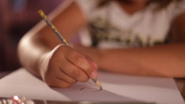 child's hand draws a pencil on paper.lose-up.