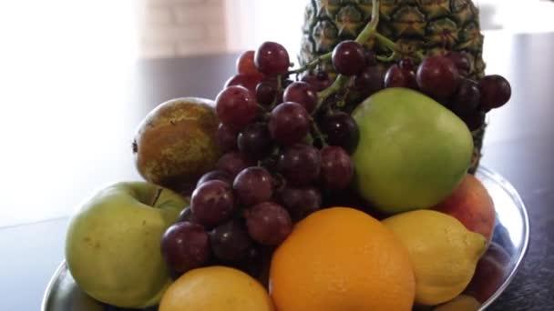Fruit plate. Pineapple, apple, red grapes, lemon, orange. Camera moves around it.