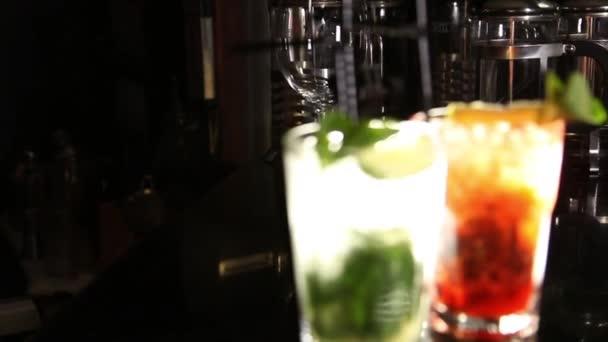 zwei Gläser Mojito-Cocktails, grün und rot. Kopierraum. Kamera fliegt rückwärts drüber