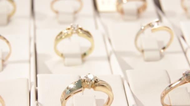 Na šperky. spousta zlatých prstenů s diamanty v okně klenotnictví. Zblízka