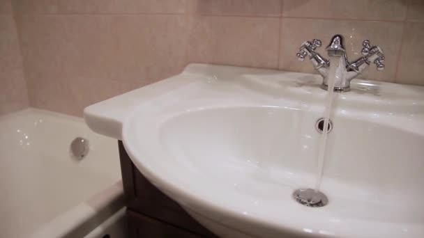 Voda teče z kohoutku v umyvadle..