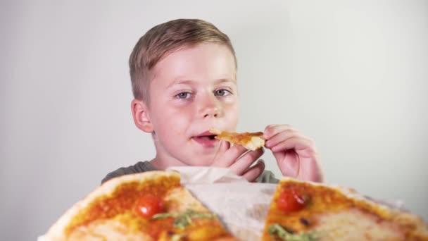 Rozkošný chlapec pojídáním pizzy s potěšením na bílém pozadí