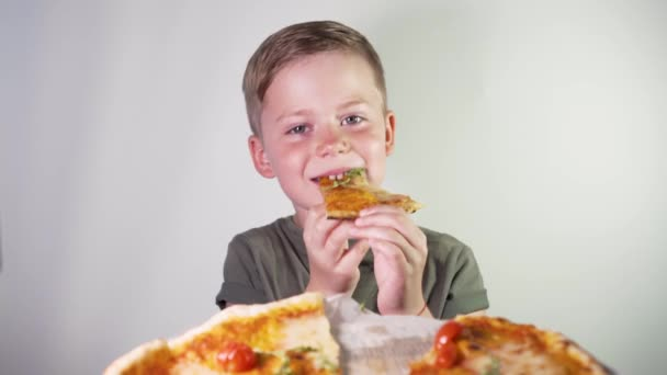 Cute Little Boy Eating Pizza With Pleasure on a White Background