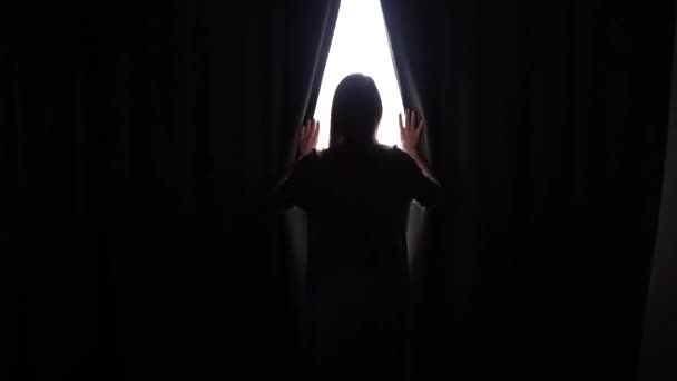 girl or woman in gray bathrobe at home open curtains and look into window